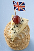 Piece of Stilton with grape and Union Jack on crackers