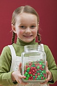 Small girl holding jar of chocolate beans