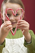 Small girl looking through heart made from two candy canes