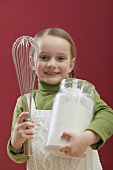 Small girl holding large jar of flour and whisk