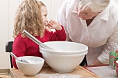 Grandmother and granddaughter baking Christmas biscuits