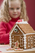 Small girl behind gingerbread house