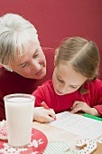 Small girl with grandmother writing Christmas letter