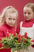 Two small girls holding Advent wreath