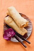 Spring rolls with orchid and chopsticks on plate