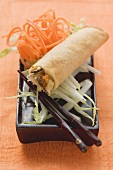 Spring roll on raw vegetables with chopsticks
