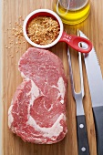 Beef steak, spice mixture, cutlery and oil