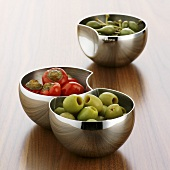 Chillies, giant capers and olives in small bowls