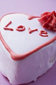 Pink heart-shaped cake with the word Love