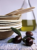 Black olives beside a stack of wooden plates