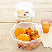 Fresh fruit in plastic containers, orange juice
