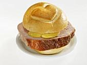 Slice of Leberkäse (type of meatloaf) in bread roll with heart