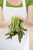 Young woman holding fresh green asparagus