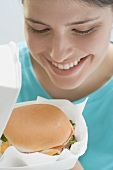 Young woman looking at cheeseburger in opened packaging