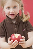 Little girl holding a partly eaten apple