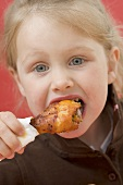 Little girl eating chicken drumstick