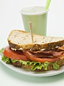 Bacon, lettuce and tomato sandwich, drink in background