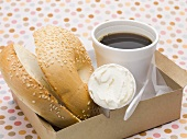 Sesame bagel with crème fraîche in cardboard box, cup of coffee