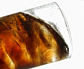 Cola with ice cubes in glass (tilted)