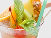 Cocktail with exotic fruit skewer and mint (close-up)