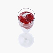 Mineral water and raspberries in stemmed glass