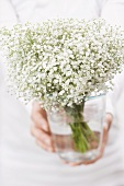 Woman holding a bouquet of gypsophila in a vase