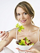 Woman eating mixed salad leaves