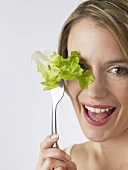 Woman holding lettuce leaf on fork in front of her eye