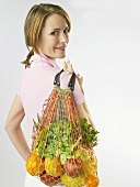 Woman holding string bag full of fruit, lettuce and herbs