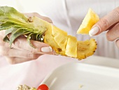 Hands holding a piece of pineapple