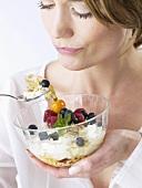 Woman eating yoghurt muesli with fruit