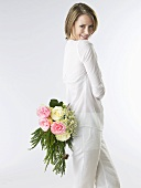 Woman holding a bouquet of flowers behind her back