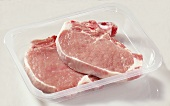 Two pork chops in plastic container