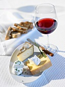 Cheese platter, glass of red wine and bread