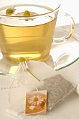 Chamomile tea in glass cup, tea bag, chamomile flowers