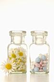 Kamillenblüten und Tabletten in Apothekerflaschen