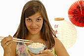 Young woman holding bowl of rice and chopsticks