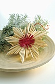 Straw star and fir sprigs on plate