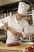 Chef seasoning meat in a commercial kitchen