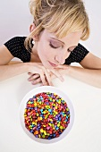 Woman looking pensively at coloured chocolate beans