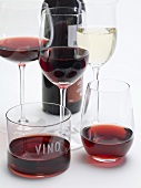 Red wine in different glasses, glass of white wine, red wine bottle