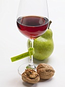 Glass of red wine with plastic label, walnuts and pear