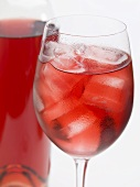 Glass of rosé wine with ice cubes beside bottle