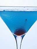 Blue Curaçao cocktail with cocktail cherry (close-up)