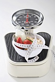 Strawberries, milk, cereal and tape measure on scales