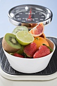 Bowl of fresh fruit on scales