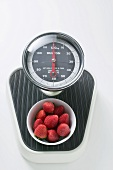 Bowl of fresh strawberries on scales