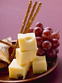Cubes of cheese with grapes and salted sticks
