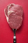 Raw beef steak on meat fork