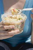 Woman eating pasta salad out of plastic tub